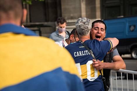 Boca Juniorsin pelipaitaan pukeutunut henkilö syleili surevaa toveriaan.