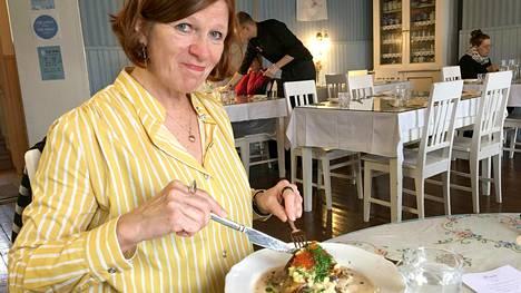 Helsingin-ystävä Erja nauttii Cafe Adelen nieriää Sagalund-museossa.