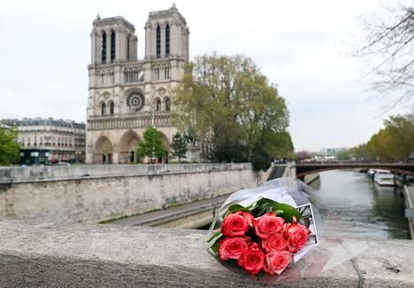 Ihmiset jättivät alkuviikon tulipalon jälkeen kukkia Notre Damen liepeille. Kuva otettu tiistaina 16. huhtikuuta.