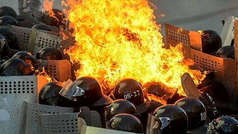 Liekit roihusivat poliisien keskellä Kiovassa tiistaina.