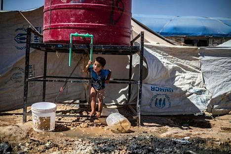 Vesihuolto, saniteettitilat ja terveydenhuolto ovat äärimmäisen puutteelliset pakolaisleirillä. Poika vesisäiliöllä al-Holissa 23. heinäkuuta.