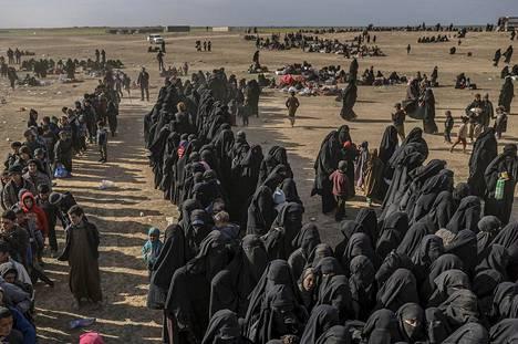 Isisin alueelta paenneet perheet kootaan turvatarkastukseen pölyiselle tasangolle Baghuzin lähellä.