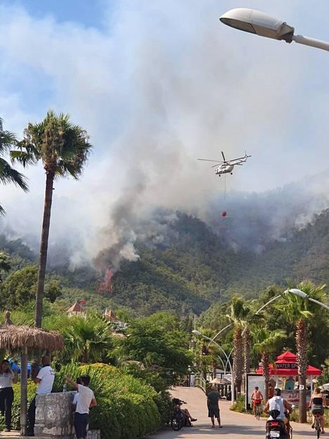 Helikopteri yritti epätoivoisesti pysäyttää rutikuivassa maastossa kulkevaa paloa.