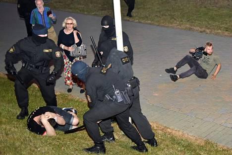 Mellakkapoliisi pidätti mielenosoittajan Minskissä.