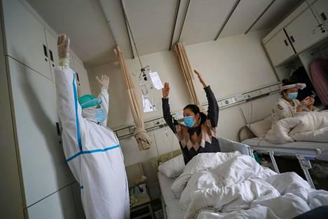 Wuhanilaisen sairaalan hoitaja neuvoi potilasta voimistelemaan.