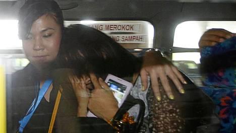 Lentoyhtiön työntekijä lohdutti Malesia Airlinesin lennolla 370 mukana olleen matkustajan kiinalaista sukulaista Kuala Lumpurin kentällä maanantaina.