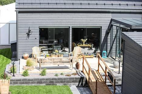 Laajalla terassilla voi nautiskella kesäpäivästä. Helpot puutarharatkaisut ovat messuilla suosiossa, ja robottiruohonleikkureita näkyy.