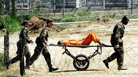 Sotilaspoliisit kärräsivät loukkaantuneen vangin Guantanamoon helmikuussa 2002.