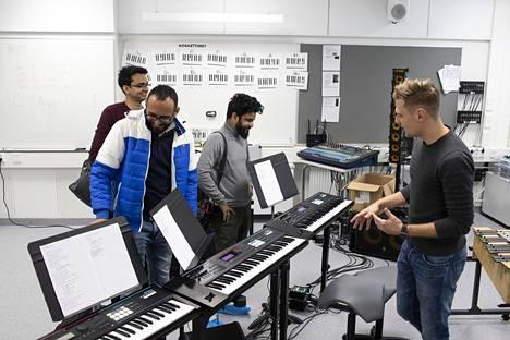 Musiikkiluokan välineistö kiinnosti erityisesti miespuolisia vieraita. Musiikinopettaja Juuso Vuorinen esitteli niitä mielellään.