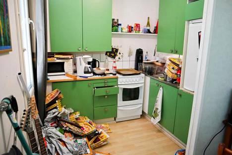 Timon keittiön lattialle on kasattu tyhjiä pakastepitsalaatikkoja ja tiskialtaaseen on koottu likaisia astioita.