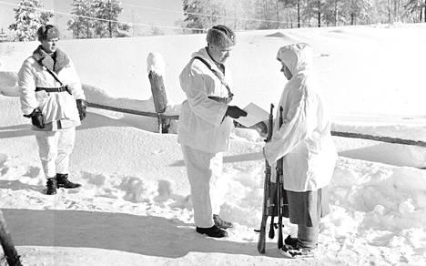 Ruotsista annetulle lahjoituskiväärille löytyi 12. Divisioonan sisällä helposti sopiva kohde, sillä Simo Häyhälle oli vähän aikaisemmin myönnetty ansioistaan taskukello. Kenraali Antero Svensson luovuttaa lahjakiväärin Simo Häyhälle.