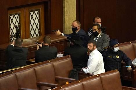 Poliisit osoittivat aseilla istuntosalissa, jota oli vandalisoitu.