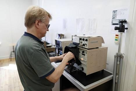 Hienomekaanikko Jukka Kelotie on alan taitava konkari, joka tarkastaa kameran valotusarvot Eiri-Kuvan vanhalla valotustesterillä.