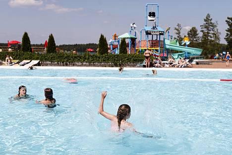 Ihmiset nauttivat vesileikeistä ja kesähelteestä vesipuisto Aquaparkissa.