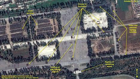 Satelliittikuvassa näkyy muun muassa sotilasjoukkoja marssimuodostelmissa, parkkeerattuja ajoneuvoja ja oikealla lukuisia panssaroituja ajoneuvoja.