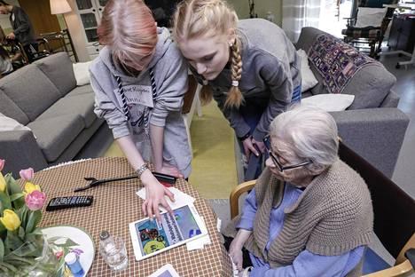 Anni Jumpponen (vas.) ja Jenna Kuisma opettavat Aila Väisäselle IPadin käyttöä.