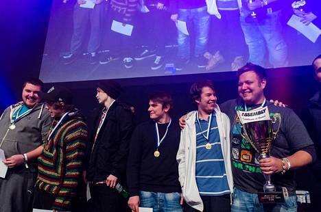 """Jalli (valkoisessa takissa) voitti vuonna 2013 Assembly Winter -tapahtuman CS-turnauksen. Pokaalia pitää kädessä ENCEn nykyinen markkinointipäällikkö Joona """"natu"""" Leppänen."""