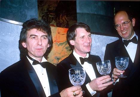 George Harrison, Michael Palin ja Denis O'Brien elokuvagaalassa Lontoossa vuonna 1986.