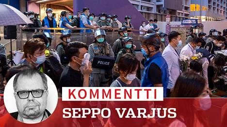 Poliisi valvoi ihmisiä, jotka olivat saapuneet muistamaan viime vuoden mielenosoituksissa kuolleita Hongkongissa.