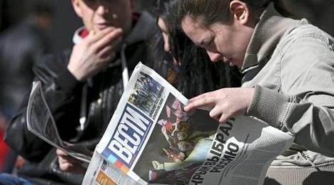 Ukrainalaisnainen lukee Simferopolissa ilmaisjakelulehteä, jonka pääotsikossa lukee: Krim valitsi Venäjän.
