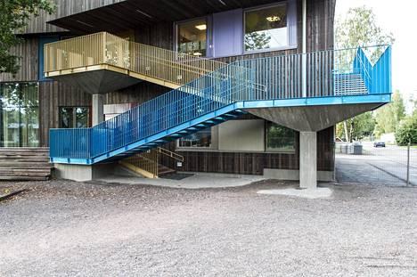 Vaaralanpuiston päiväkodin ulkoseinien pinnat ovat tummat. Väriä ulkoasuun tuo portaiden kaiteiden kirkkaat värit.