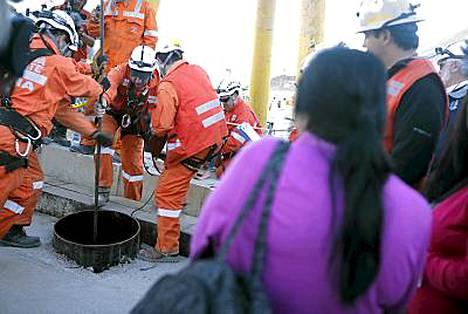 Miehiä nostettiin kaivoksesta pelastuskapselilla. Mainarin sukulainen seuraa vieressä pelastustoimia.