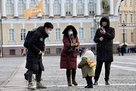 Kiinalaiset turistit tutkivat Pietaria hengityssuojaimet kasvoillaan.