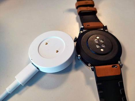 Kello napsahtaa kiinni latausalustaan magneetilla. Kaapeli kiinnittyy usb-c-porttiin, mutta kaapelia ei tule paketin mukana.