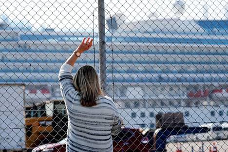 Nainen vilkuttaa aluksen parvekkeella seisovalle matkustajalle samalla, kun he puhuvat puhelimessa.
