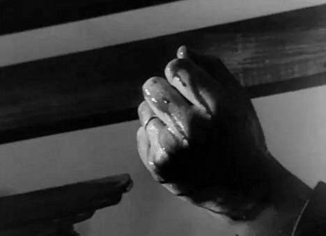 Lähikuva kaatuneen sotilaan nyrkkiin puristuneesta kädestä.