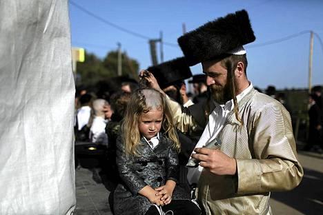 Ultraortodoksijuutalainen mies leikkaa kolmevuotiaan lapsensa hiuksia Lag Baomer -juhlapäivänä. Lag Baomer kunnioittaa rabbi Shimon Bar Yochain perintöä, joka on yksi tärkeimmästä juutalaisista pyhimyksistä. Päivän traditioon kuuluu, että kolmevuotiaat pojat saavat tuolloin ensimmäisen hiustenleikkuunsa.