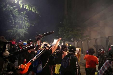 Mielenosoittajat puhalsivat kyynelkaasua lehtipuhaltimella kohti poliiseja.