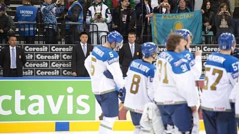 Kazakstanin pelaajia allapäin joukkueen hävittyä vuoden 2014 MM-kilpailuissa Suomelle. Taustalla näkyvät Kazakstanin silloiset valmentajat Ari-Pekka Selin (vas.) ja Raimo Helminen.
