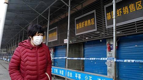 Nainen on peittänyt suunsa ja nenänsä hengityssuojaimella kävellessään viranomaisten sulkeman kalatorin ohi.
