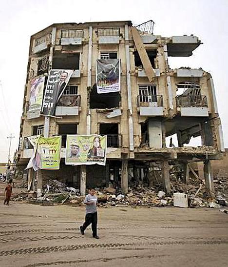 Vaalijulisteet roikkuivat al-Qaidan tuhoaman rakennuksen seinillä Ramadissa, Irakin Anbarissa perjantaina.