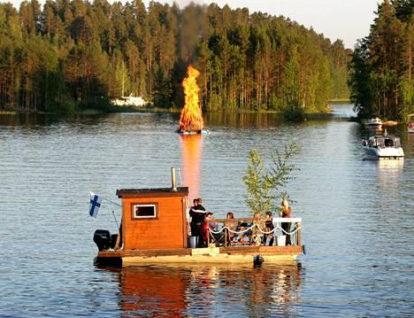 Kuva Punkaharjulta vuodelta 2007 voisi olla suomalaisen juhannuksen koko kuva: on järvi, poltetaan komeaa kokkoa, on kaadettu juhannuskoivu, Suomen lippu heilahtelee tuulessa, ollaan sopuisasti porukalla, syödään ehkä makkaraa...