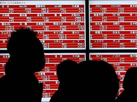 Jalankulkijat ohittavat pankkiiriliikkeen Japanissa. Japanin Nikkei-indeksi vahvistui tukevasti perjantaina.