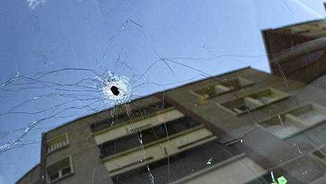 Luodinreikä piirityksessä kuolleen sarjamurhat tunnustaneen miehen asunnon pihalle pysäköidyn auton tuulilasissa.