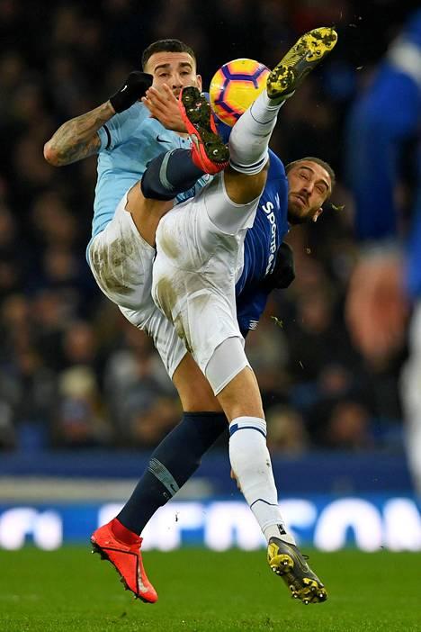 Manchester Cityn Nicolas Otamendi (vas.) ja Evertonin Cenk Tosun taistelivat pallosta ketterästi.