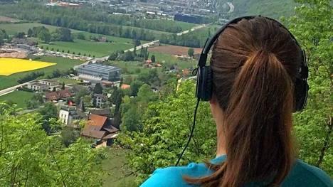 Aivotutkijan mukaan tietokirjojen kuunteleminen on loistavaa aivojumppaa. Kuvassa Iiris Tulimaa kuuntelemassa äänikirjaa kotimaisemissaan Sveitsissä.