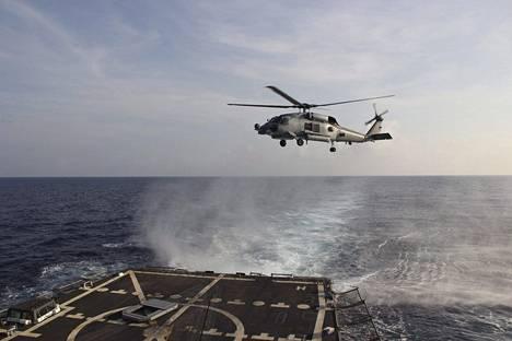 Alunperin MH370-lentoa etsittiin muun muassa pohjoisesta Siaminlahdelta, mutta pian tutkinta kohdistettiin täysin päinvastaiseen suuntaan satelliittitietojen perusteella. Kuvassa Yhdysvaltain Seahawk-helikopteri Siaminlahdella koneen katoamisen jälkeisenä päivänä.