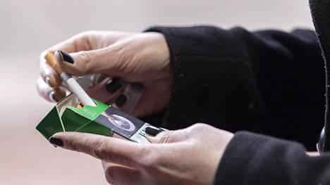 Nainen ottaa mentolisavuketta tupakka-askista Helsingissä 10. maaliskuuta 2020.