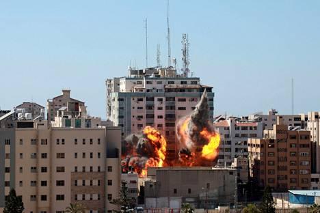 Jala Tower -talon juurella leimahti hetkeä ennen kuin se sortui murskaksi maan tasalle lauantaina Gazassa.