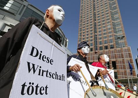 """Ihmiset osoittivat mieltä Deutsche Bankin toimintaa vastaan tänään. Kyltissä lukee """"Tämä talous tappaa""""."""