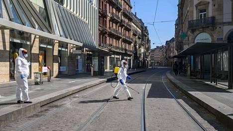 Suoja-asuun pukeutunut kaupungin työntekijä desinfioi raitiovaunupysäkkejä Strasburgissa keskiviikkona.