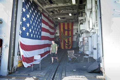 """Helikopterihangaaria koristaa muun muassa valtava Yhdysvaltain lippu. Taustalippuun on kirjailut Jason Dunhamin nimikirjaimet ja teksti """"Don't tread on me""""."""
