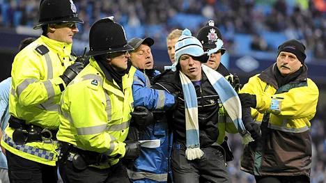 City-kannattaja Matthew Stottia talutettiin pois kentältä Manchesterin derbyn loppuhulinoinneissa.