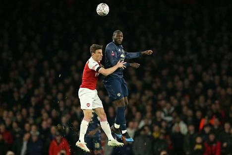Arsenalin Laurent Koscielny ja Manchester Unitedin Romelu Lukaku ilmataistelussa.