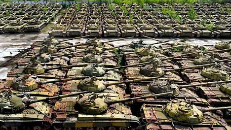Hylättyjen panssarivaunujen rivistöjen väleissä kasvaa jo puita ja pensaitakin.