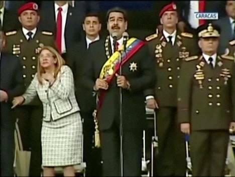 Venezuelan kansallisen tv-kanavan lähetyksessä näkyy, kuinka Maduro ja hänen taustajoukkonsa hätkähtävät räjähdyksiä.